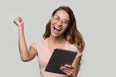 Mujer feliz en los vidrios que sostienen la tableta digital que grita celebrando triunfo fotografía de archivo libre de regalías
