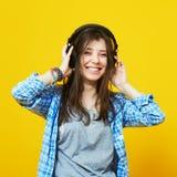 Mujer feliz en música que escucha de los auriculares Foto de archivo