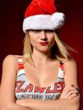 Mujer feliz en muchacha enojada del sombrero de Papá Noel de la Navidad en fondo rojo Imagen de archivo libre de regalías