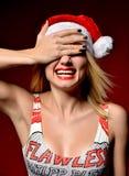 Mujer feliz en muchacha sonriente del sombrero de Papá Noel de la Navidad en backgroun rojo Imagen de archivo libre de regalías