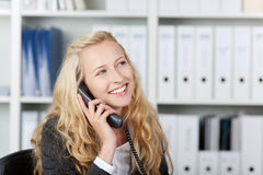 Mujer feliz en oficina que habla en el teléfono Foto de archivo libre de regalías