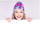 Mujer feliz en prendas de vestir exteriores del invierno sobre la bandera blanca Imagen de archivo