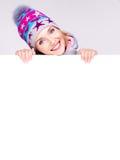 Mujer feliz en prendas de vestir exteriores del invierno sobre la bandera blanca Foto de archivo