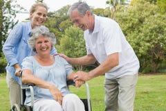 Mujer feliz en silla de ruedas con la hija y el marido foto de archivo