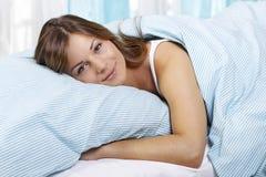 Mujer feliz en su cama Imágenes de archivo libres de regalías