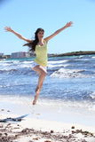 Mujer feliz en tiro en suspensión en la playa Foto de archivo libre de regalías