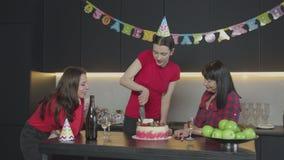 Mujer feliz en torta de cumpleaños del corte del sombrero del partido almacen de metraje de vídeo