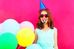 Mujer feliz en un casquillo del cumpleaños con los globos coloridos de un aire sobre fondo rosado Imagen de archivo