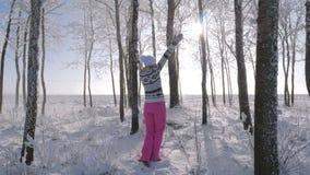 Mujer feliz en un invierno fabuloso Forest Raises Her Hands Up y torneado alrededor almacen de video