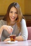 Mujer feliz en una cafetería con una taza de té Fotos de archivo libres de regalías