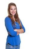 Mujer feliz en una camisa azul con los brazos cruzados Imágenes de archivo libres de regalías