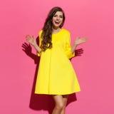 Mujer feliz en vestido amarillo con los brazos extendidos imagenes de archivo