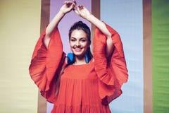 Mujer feliz en vestido anaranjado con las mangas hermosas Imágenes de archivo libres de regalías