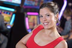 Mujer feliz en vestido rojo en el casino imagen de archivo