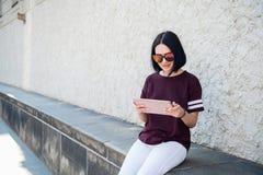 Mujer feliz en vidrios usando la PC de la tableta en la calle fotografía de archivo libre de regalías