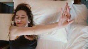 Mujer feliz fresca que miente en cama y estirar La muchacha atractiva despierta por la mañana, sonriendo metrajes