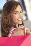 Mujer feliz hermosa con el bolso de compras rosado Fotos de archivo libres de regalías