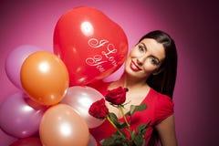 Mujer feliz hermosa con el globo del día de tarjetas del día de San Valentín en fondo rosado Imagen de archivo libre de regalías