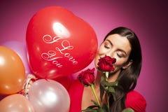 Mujer feliz hermosa con el globo del día de tarjetas del día de San Valentín en fondo rosado Foto de archivo libre de regalías