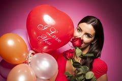 Mujer feliz hermosa con el globo del día de tarjetas del día de San Valentín en fondo rosado Fotografía de archivo libre de regalías