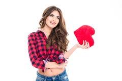Mujer feliz hermosa con el pelo rizado largo que lleva a cabo el corazón rojo Imagenes de archivo