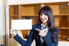 Mujer feliz hermosa con la tarjeta vacía en oficina Fotos de archivo