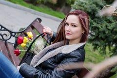 Mujer feliz hermosa con los tulipanes en un bolso Imagenes de archivo