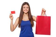 Mujer feliz hermosa de la sonrisa que sostiene el panier y que muestra la tarjeta del crédito en blanco, venta, aislada en el fon Imágenes de archivo libres de regalías