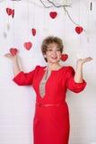 Mujer feliz hermosa de 50s en vestido rojo Día del `s de la tarjeta del día de San Valentín Foto de archivo