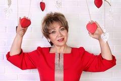 Mujer feliz hermosa de 50s en vestido rojo Día del `s de la tarjeta del día de San Valentín Imágenes de archivo libres de regalías