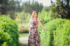Mujer feliz hermosa del retrato que goza del olor en un jardín floreciente de la primavera floreciente Muchacha sonriente brillan foto de archivo
