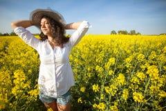 Mujer feliz hermosa en campo del canola en día soleado Foto de archivo libre de regalías