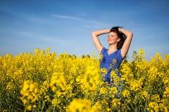 Mujer feliz hermosa en campo del canola en día soleado Foto de archivo