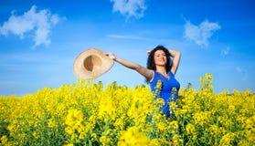 Mujer feliz hermosa en campo del canola en día soleado Fotografía de archivo