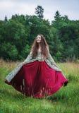 Mujer feliz hermosa en el baile medieval del vestido al aire libre foto de archivo