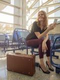 Mujer feliz hermosa en la sala de espera del aeropuerto Tiempo de vacaciones Foto de archivo libre de regalías