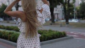 Mujer feliz hermosa en pelo que lanza del vestido en el callejón de la ciudad del verano, a cámara lenta almacen de video