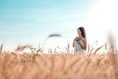 Mujer feliz hermosa en un campo, tarde soleada, vestido blanco Pelo hermoso, piel bronceada, concepto de disfrutar de la naturale Fotografía de archivo libre de regalías