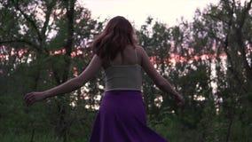 Mujer feliz hermosa joven con el pecho grande que circunda descalzo en el bosque en una falda púrpura en el tiempo crepuscular almacen de video