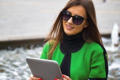 Mujer feliz hermosa que se sienta al aire libre y que usa una tableta Imagenes de archivo