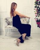 Mujer feliz hermosa que se sienta y que presenta en el banco en la moda Fotografía de archivo libre de regalías