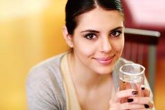 Mujer feliz hermosa que se sostiene de cristal con agua Fotos de archivo