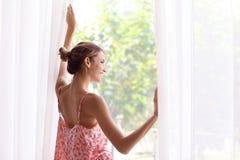 Mujer feliz joven cerca de la ventana en casa fotos de archivo