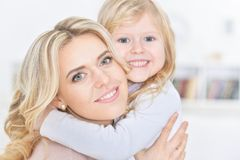 Mujer feliz joven con el abarcamiento de la niña Imágenes de archivo libres de regalías