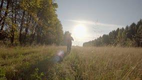 Mujer feliz, joven con el funcionamiento de la sonrisa La mujer corre en la cámara en un campo amarillo almacen de metraje de vídeo