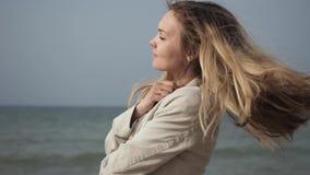 Mujer feliz joven con el pelo largo en un baile beige del primer de la capa en la playa del mar metrajes