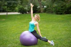 Mujer feliz joven con la bola de la aptitud, al aire libre Fotos de archivo libres de regalías