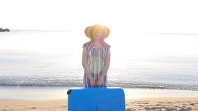 Mujer feliz joven con la maleta grande en la playa almacen de metraje de vídeo
