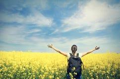 Mujer feliz joven con la mochila en un campo de la violación amarilla Imagenes de archivo