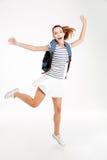 Mujer feliz joven con la mochila que salta y que celebra éxito Imagenes de archivo